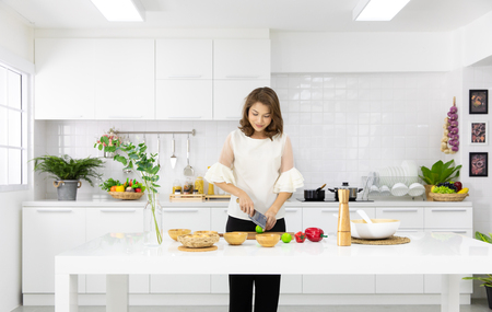 Beautiful Asian woman showing her new kitchen decoration and play with fake fruits and vegetables. Concept to modern housewife. Stockfoto - 112648846