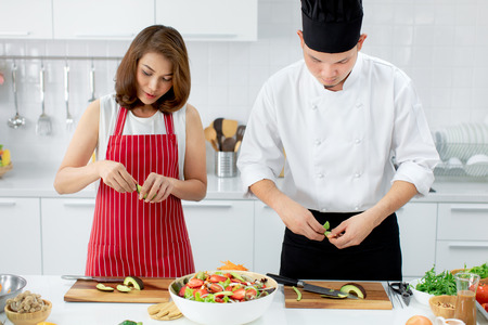 Beautiful Asian woman in red apron learning how to cook and mix vegetable salad in big bowl, teaching by Asian chef in white modern kitchen.