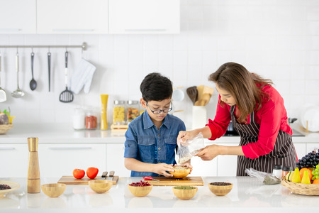 Beautiful Asian woman in red shirt and black  apron teaching her son how to put grains into wood bowl in white clean modern kitchen.