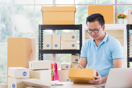 Young Asian businessman in casual shirt write on parcels,  working in simple house office look like doing startup business. Concept for online marketing, SME and home base workplace. Banque d'images
