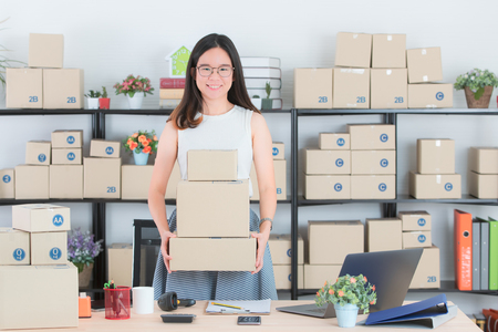 Young and beautiful Asian woman hold parcals reday to ship with smiling face happy to orders online customers in the homeoffice. Concept for home base business and startup ownership. Stock Photo