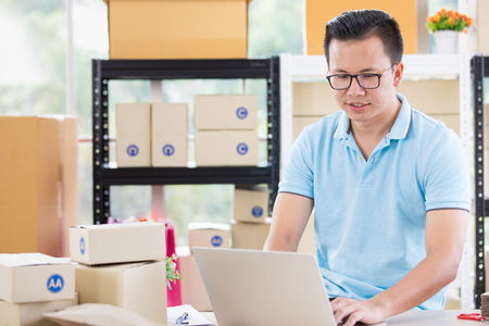 Young Asian businessman in casual shirt look at notebook among several parcels,  working in simple house office look like doing startup business. Concept for online marketing, SME and home base workplace. Stock Photo