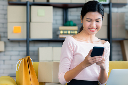 Young Asian beautiful girl is happy smiling to shopping online with smartphones and other order items she buys around her. Concept technology makes us live more comfortable and easy to tread.