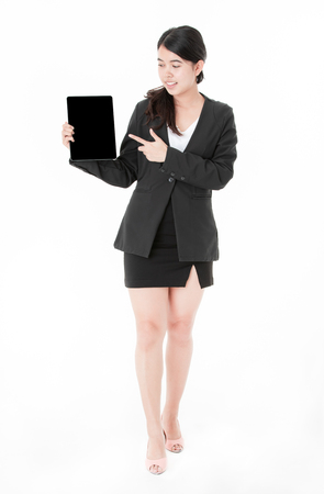 Portrait Asian young businesswoman showing tablet and finger pointing to blank screen,  isolated on white background. Stock Photo