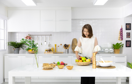 Beautiful Asian woman showing her new kitchen decoration and play with fake fruits and vegetables. Concept to modern housewife.