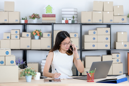 Young and beautiful Asian woman using smartphone with smiling face in office. Concept for home base business and startup ownership.