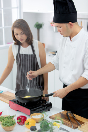 Asian male chef demonstrating how to cook for beautiful student with smoke from black pan in white clean modern kitchen.