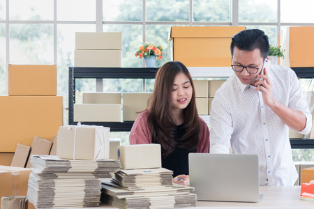 Young Asian couple business  working in simple house office look like doing startup business. Concept for online marketing, SME and home base workplace. Stock Photo
