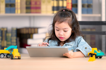 Lovely cute little Asian girl in jeans shirt using tablet and toys on desk. Concept for funny activity of young kids free time. Stock Photo