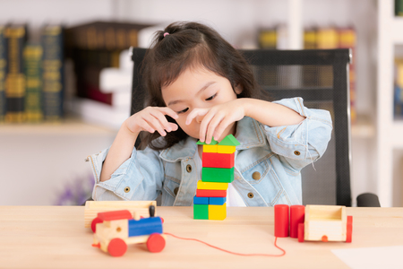 Lovely cute little Asian girl in jeans shirt playing wood block toys on desk. Concept for funny activity of young kids in free time. Stock Photo