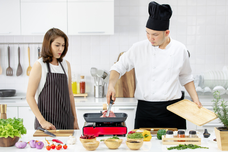 Beautiful Asian woman in black apron feel wondering while seeing male chef cooking meat in pan to make steak in modern white clean kitchen. Many ingredients on table. Stock Photo