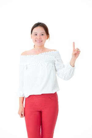 Asian woman beautiful smile in casual dress standing fingers point up portrait close up studio shot on the white backdrop.