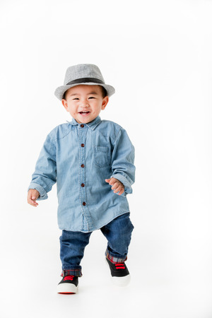 One year old Asian baby boy smiling in jeans shurt walking and looking to camera  isolated on white background studio shot.