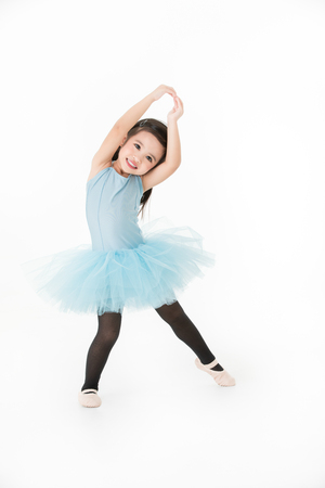 Cute Asian girl in light blue dress preforming ballet with smiling face, isolated on white background.