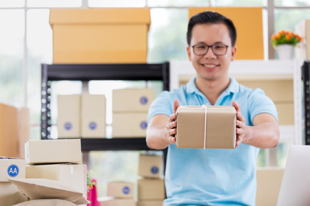 Asian businessman in casual shirt hold in parcels on hand,  working in simple house office look like doing startup business. Concept for online marketing, SME and home base workplace.