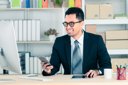 Asian businessman in suit smile looking to smartphones and sitting in office. Small Business Startup Initiative.