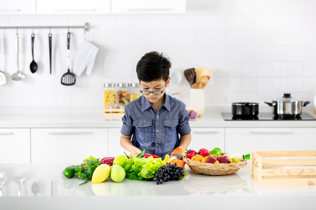 Young Asian boy looking to pile of fake fruits and vegetables in white clean modern kitchen.