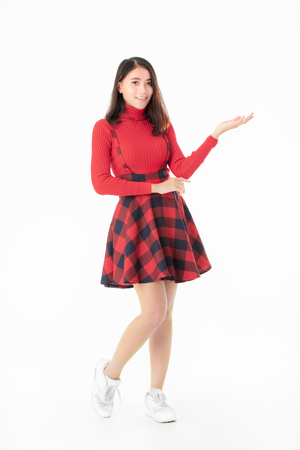 Beautiful Asain portrait woman in red casual dress standing and looking camera like holding something isolated on white background.