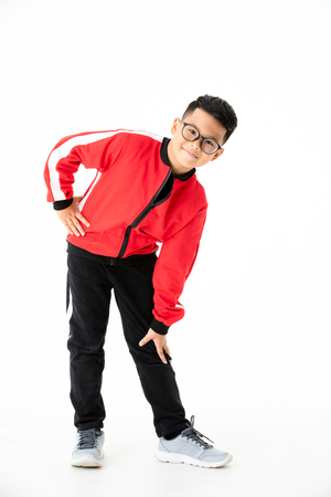 Young and handsome young Asian boy in red and black cloths standing and looking at camera with smile face. Concept for exercise for good health kid. Standard-Bild