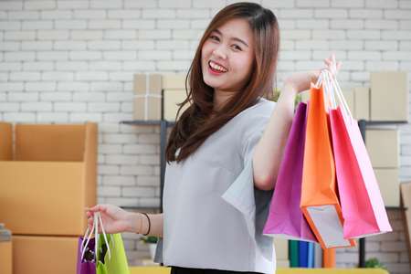 Young and beautiful Asian woman holding several colorful shopping bags with very happy smiling face. Concept for luxury or extravagant lifestyle of modern people. 版權商用圖片 - 112649551