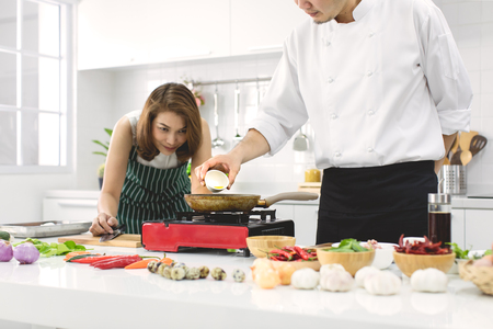 Beautiful Asian woman in red apron looking and noticing how to make fried egg, teaching by chef in white clean modern kitchen.