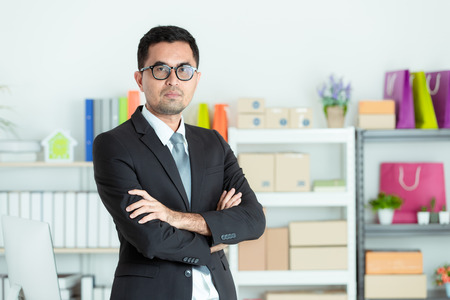 Asian businessman in suit looks good standing cross his arm in front of office desk. Small Business Startup Initiative.
