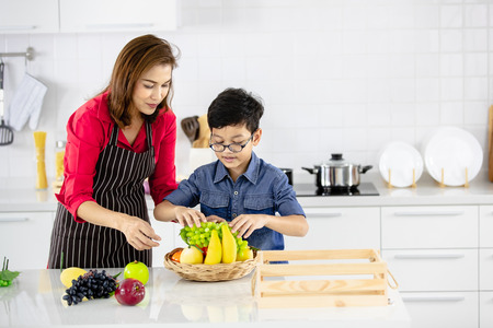 Beautiful Asian woman in red shirt and black  apron teaching her son how to arrange fake fruits and vegetables for decoration in white clean kitchen. 版權商用圖片 - 112649623