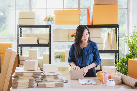Young and beautiful Asian woman standing among several boxes and checking parcels, working in the house office. Concept for home base business and startup ownership. Stock Photo - 112649624