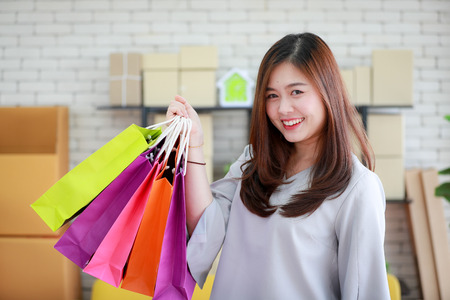 Young and beautiful Asian woman holding several colorful shopping bags with very happy smiling face. Concept for luxury or extravagant lifestyle of modern people.