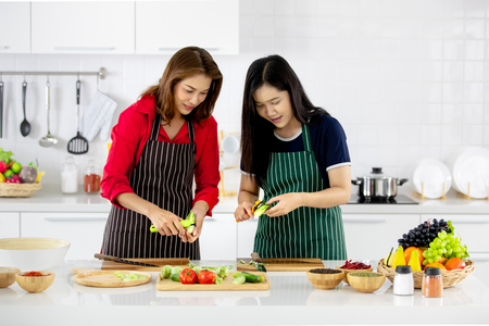Beautiful Asian woman in red shirt and black  apron teaching her daughter how to prepare vegetables for cooking in white clean modern kitchen. Imagens