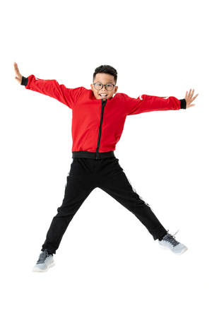 Asian boy in a red sport  is jumping on a white backdrop. Portrait and isolated in studio shot. Exercise ideas make children healthy. Stock Photo