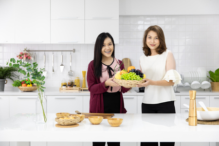 Two beautiful young and middle age Asian woman working together in new modern kitchen, arranging basket of fake vegetables for decoration. Concept for love of family, mother and daughter or sisterhood.
