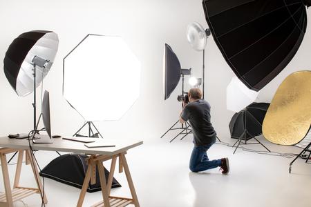 Fotograf, der in einem modernen Lichtstudio mit vielen Arten von Blitz und Zubehör arbeitet. in einen leeren Bereich zu bringen, in dem es aussieht wie auf jemanden geschossen. Idee zum Hinzufügen von Personen oder Objekten zum Foto.
