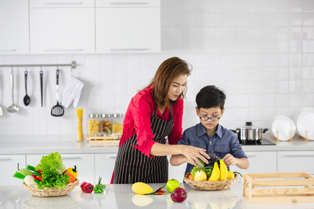 Beautiful Asian woman in red shirt and black  apron teaching her son how to arrange fake fruits and vegetables for decoration in white clean kitchen. 版權商用圖片 - 112649647