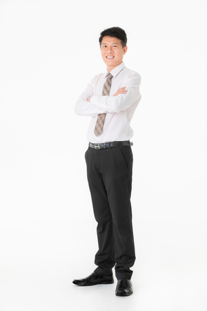 Portrait of Asian businessman in shirt standing and smiling, ing, crossed his arm, isolated on white background.