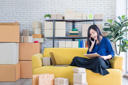 Young and beautiful Asian woman sitting among several boxes and checking parcels on the yellow sofa, working in the house office. Concept for home base business and startup ownership.