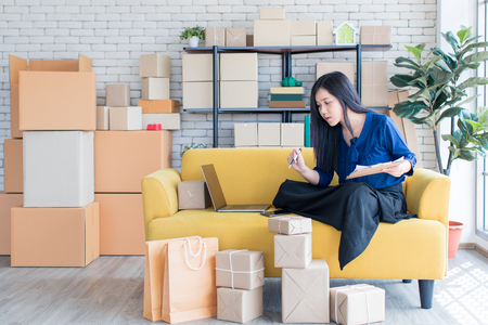 Young and beautiful Asian woman sitting among several boxes and checking parcels on the yellow sofa, working in the house office. Concept for home base business and startup ownership. 版權商用圖片 - 112649659
