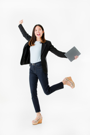 Asian businesswoman in black suit jumping with celebrating successful joyful isolated on white background studio shot.
