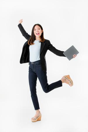 Asian businesswoman in black suit jumping with celebrating successful joyful isolated on white background studio shot. 版權商用圖片 - 112649835