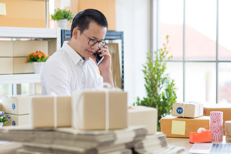 Young Asian businessman in casual shirt use calling smartphone,  working in simple house office look like doing startup business. Concept for online marketing, SME and home base workplace. Stock Photo