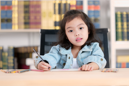 Lovely cute little Asian girl in jeans shirtdrawing on desk. Concept for funny activity of young kids free time. Imagens
