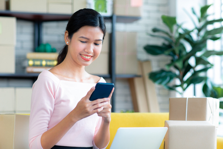 Young Asian beautiful girl is happy smiling to shopping online with smartphones and other order items she buys around her. Concept technology makes us live more comfortable and easy to tread. 版權商用圖片 - 112649840