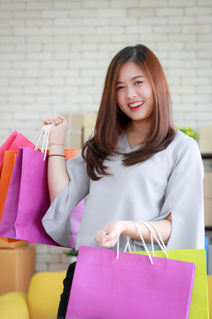 Young and beautiful Asian woman holding several colorful shopping bags with very happy smiling face. Concept for luxury or extravagant lifestyle of modern people. 版權商用圖片 - 112649842