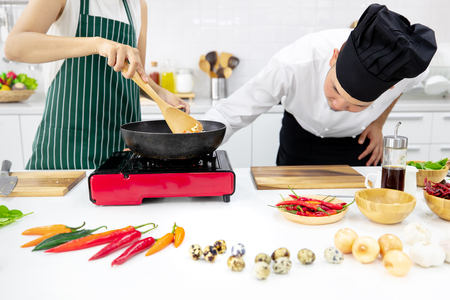 Chef in black hood teaching woman in black apron how to cook fried rice in white clean modern kitchen with many kinds of ingredients on table. 版權商用圖片 - 112649845