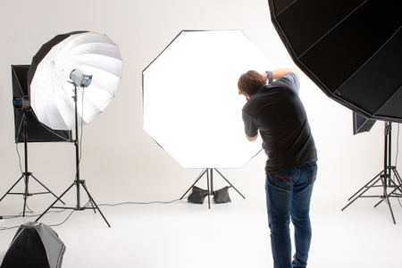 Photographer  working in modern lighting studio with many kinds of flash and accessories. taking to empty area in look like shot to someone. Idea for adding people or object to photo. 版權商用圖片 - 112649846