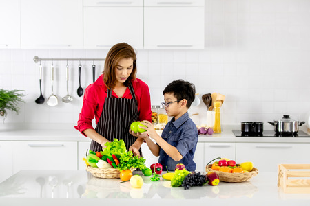 Beautiful Asian woman in red shirt and black  apron teaching her son how to arrange fake fruits and vegetables for decoration in white clean kitchen. 版權商用圖片 - 112649849