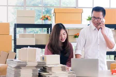 Young Asian couple business  working in simple house office look like doing startup business. Concept for online marketing, SME and home base workplace. Imagens