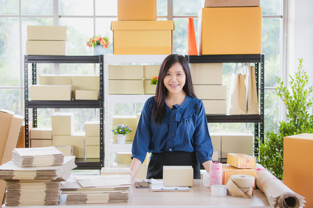 Young and beautiful Asian woman standing among several boxes and checking parcels, working in the house office. Concept for home base business and startup ownership.