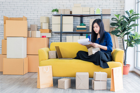 Young and beautiful Asian woman sitting among several boxes and checking parcels on the yellow sofa, working in the house office. Concept for home base business and startup ownership. 版權商用圖片 - 112649854