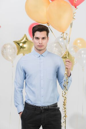 Handsome young caucasian man look serious and staid holding colorful festive balloons, portrait studio shot, white background.